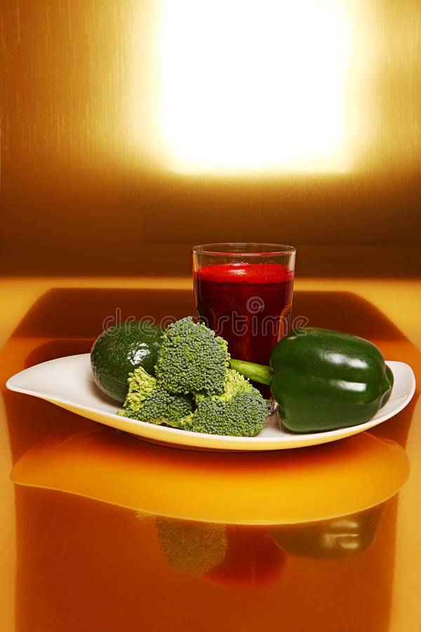 Rödbetasmoothie i exponeringsglas, nära ny broccoli, paprika, avokado royaltyfri bild