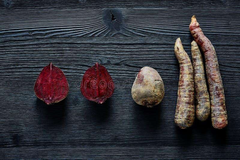 Rödbetor och morötter på mörka wood speciala foods på mörkt trä royaltyfri foto