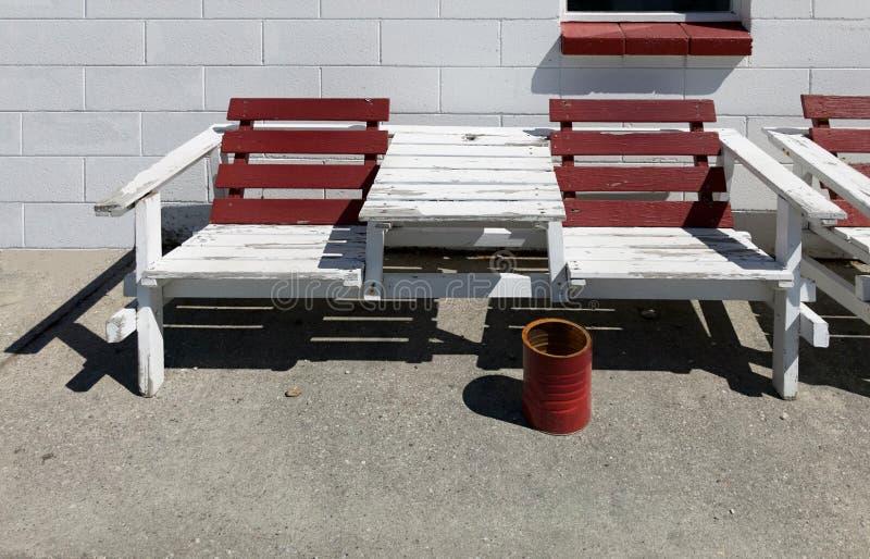 Rödbrun och vit färg målade träutomhus- sommarbänkstol mot vit bakgrund för väggen för det konkreta kvarteret för tegelsten och d arkivbilder