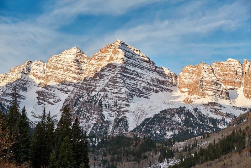 Rödbruna Klockor berg i snö på soluppgång arkivbild