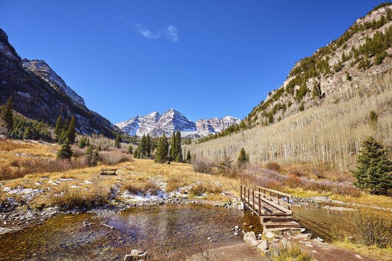 Rödbrunt Klockor berglandskap med träbron royaltyfria bilder