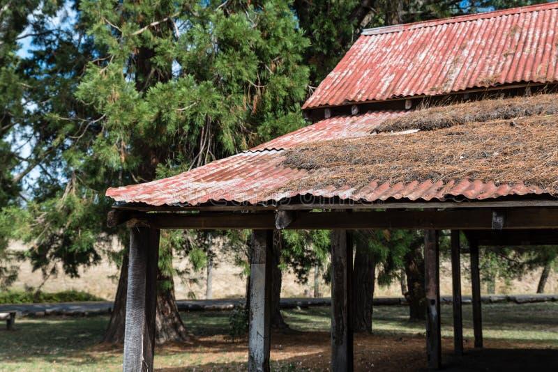 Rödbrunt rött tenn- tak på en ladugård/skydd arkivfoton