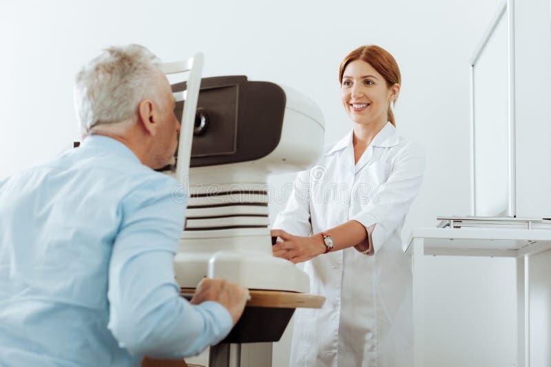 Rödhårig ögondoktor som ler, medan analysera ögonsikt av patienten royaltyfri foto