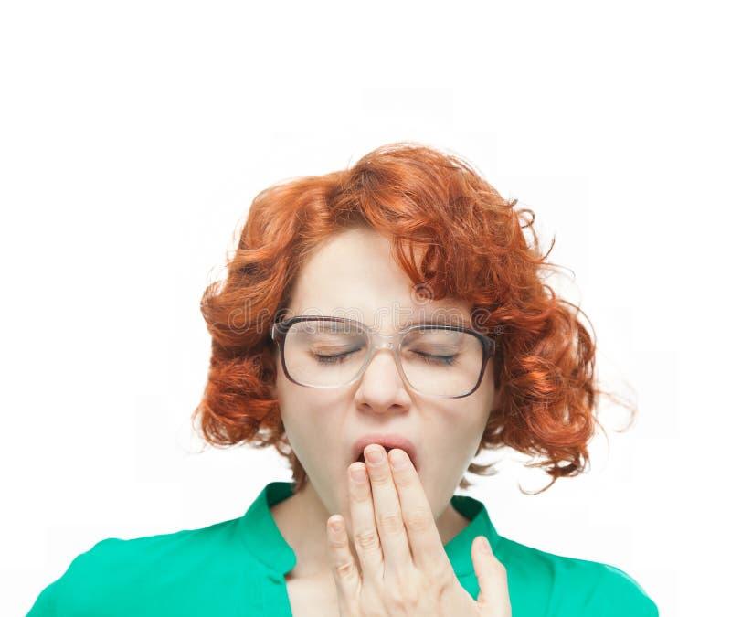 Rödhårig flicka, i att gäspa för exponeringsglas royaltyfri bild