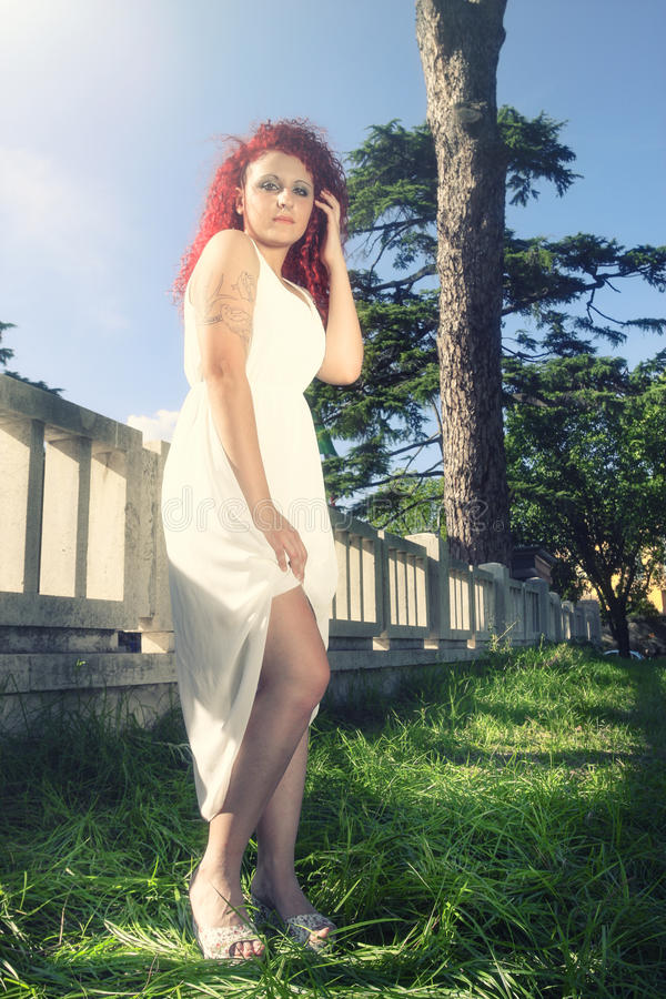 Rödhårig flicka i det vita klänninganseendet på gräset i parkera royaltyfri bild