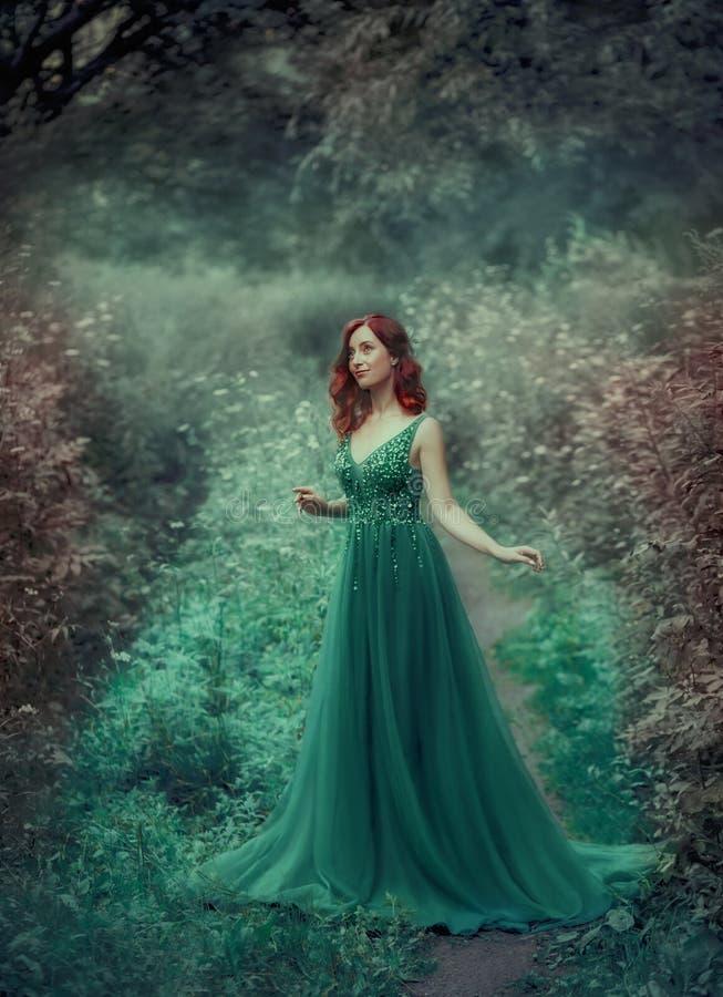 Rödhårig flicka i en gräsplan, smaragd, lyxig klänning i golvet, med ett långt drev Prinsessan går i en fe arkivbilder