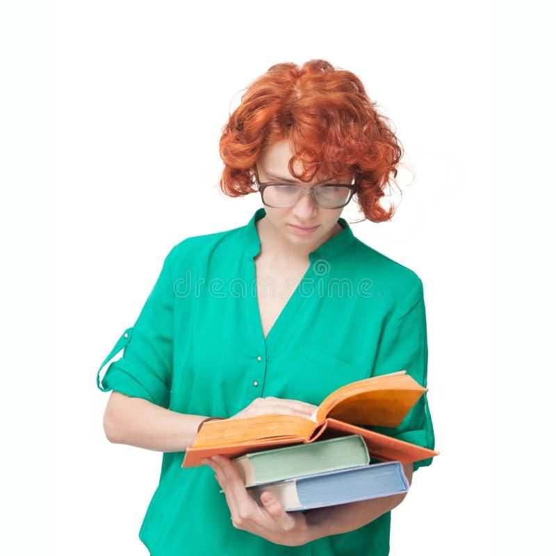 Rödhårig flicka i exponeringsglas med böcker arkivfoto
