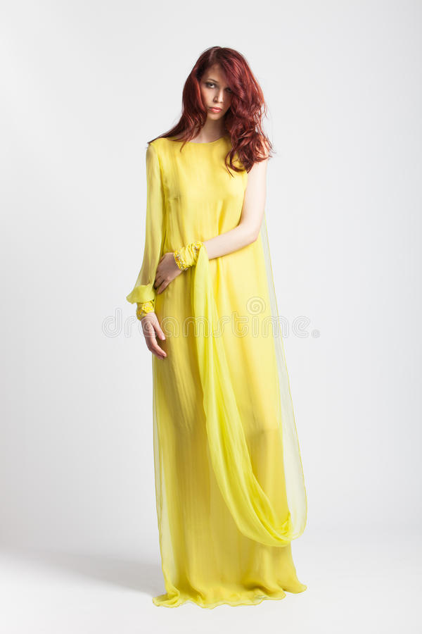 Rödhårig flicka i lång elegant gul klänning fotografering för bildbyråer