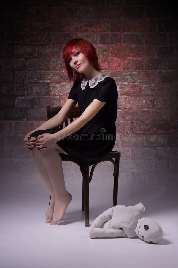 Rödhårig flicka med dockan i en dyster atmosfär arkivfoton