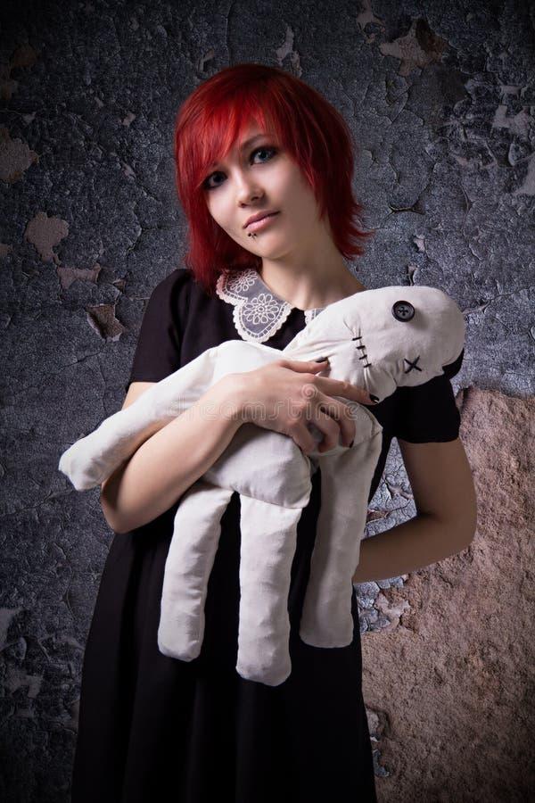 Rödhårig flicka med en trasdocka fotografering för bildbyråer