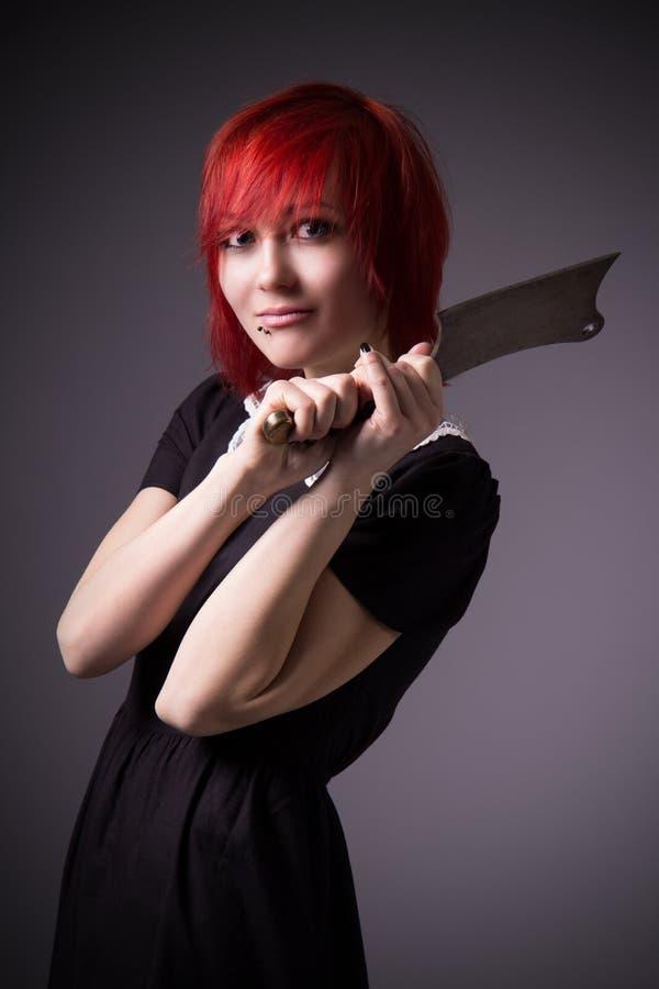 Rödhårig flicka med en yxa royaltyfria bilder