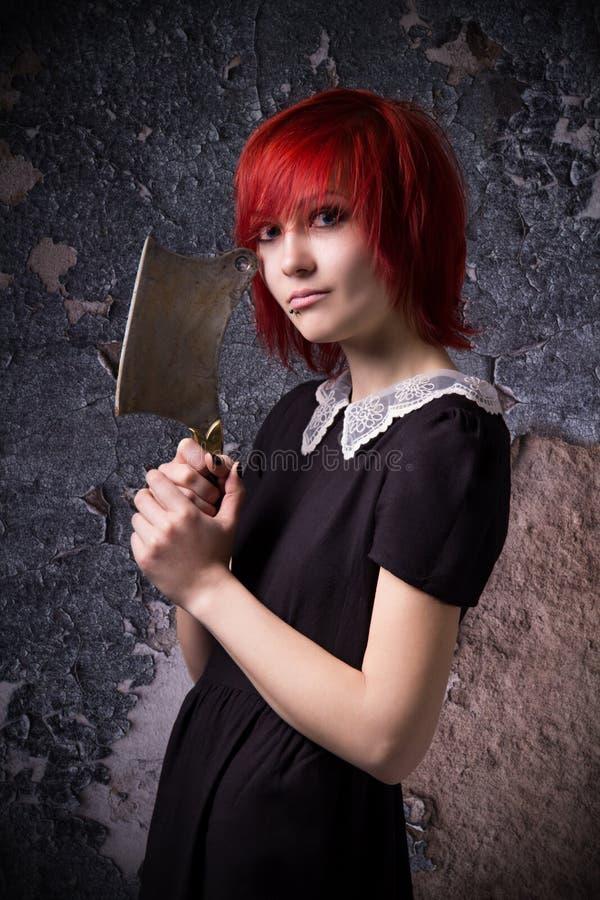 Rödhårig flicka med en yxa arkivbild