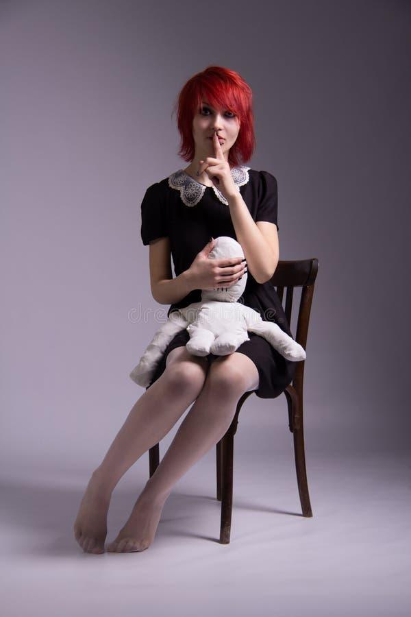 Rödhårig flicka och docka på en stol fotografering för bildbyråer