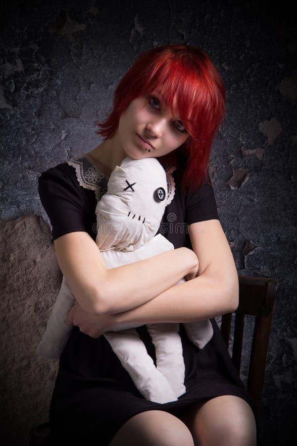 Rödhårig flicka och docka på en stol royaltyfri foto
