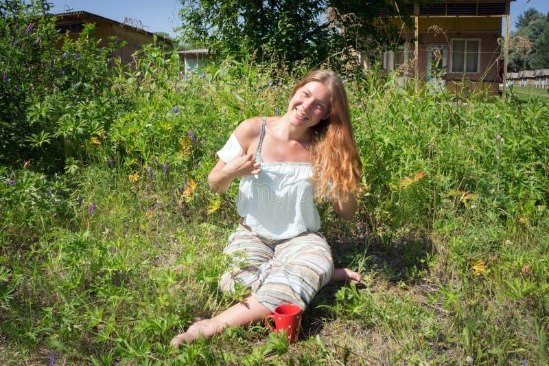 Rödhårig flicka som sitter på gräset med en röd kopp kaffe på bakgrunden av att campa i sommarmorgon royaltyfri foto