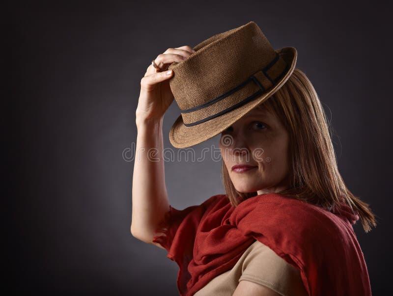 Rödhårig kvinna i brun hatt royaltyfria bilder