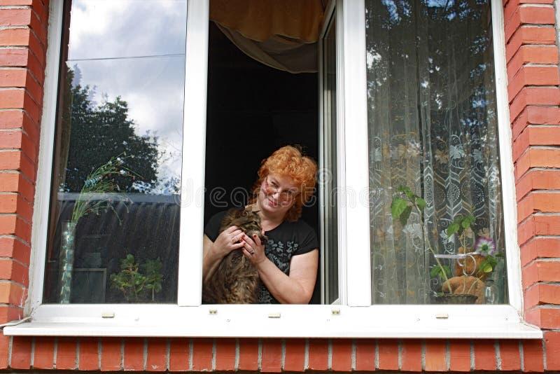 Rödhårig kvinna med katten bak öppet fönster arkivfoton
