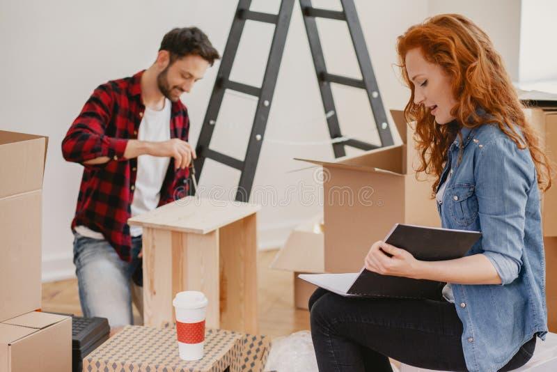 Rödhårig kvinna som ser fotoalbumet, medan möblera en lägenhet royaltyfria bilder