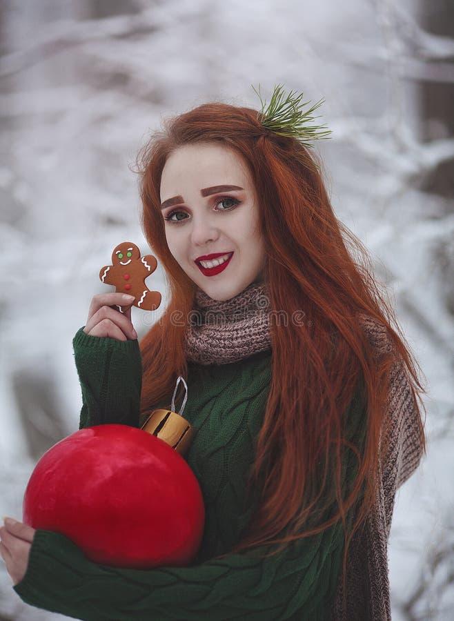 Rödhårig långhårig le flicka med en röd boll för enorm jul som äter ljust rödbrun kakor En ung kvinna med rött hår arkivbilder
