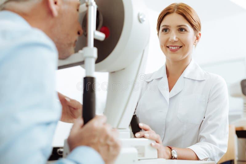 Rödhårig le ögondoktor som tycker om processen av arbete arkivfoton