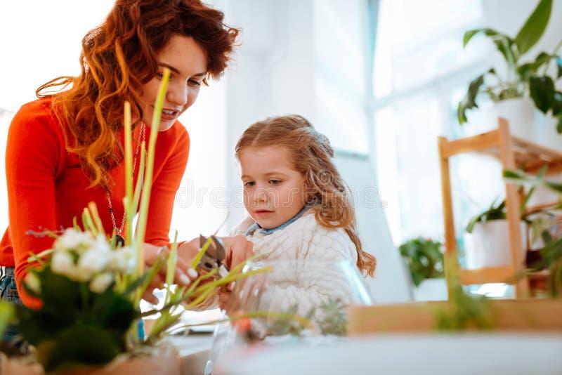 Rödhårig mamma som klipper torra kanter av den hem- växten med dottern royaltyfria foton