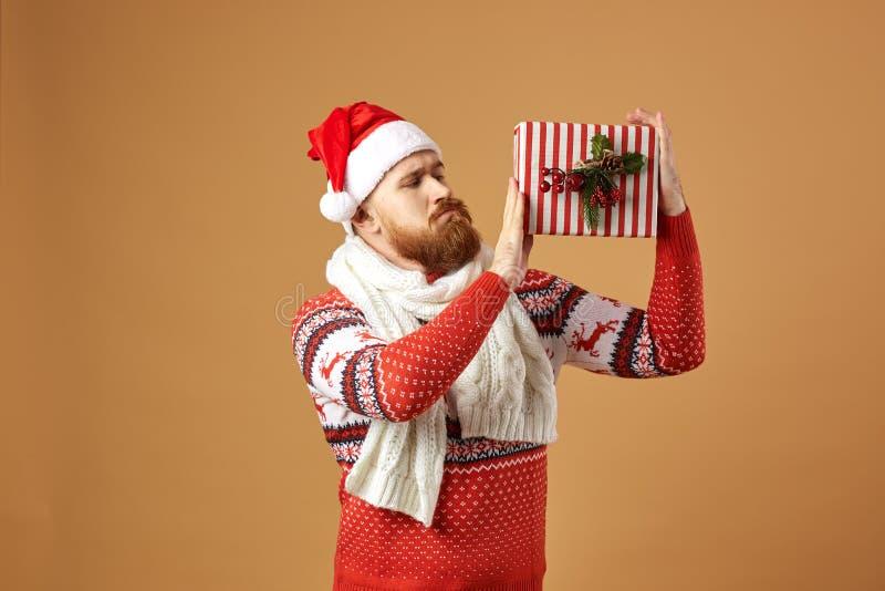 Rödhårig man med det iklädda skägget en röd och vit tröja med hjortar, en vit stucken halsduk och en hatt av Santa Claus royaltyfri fotografi
