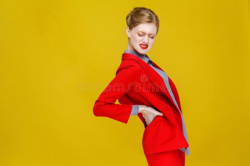 Rödhårig manaffärskvinnan i röd dräkt har njure att smärta eller dra tillbaka royaltyfri fotografi