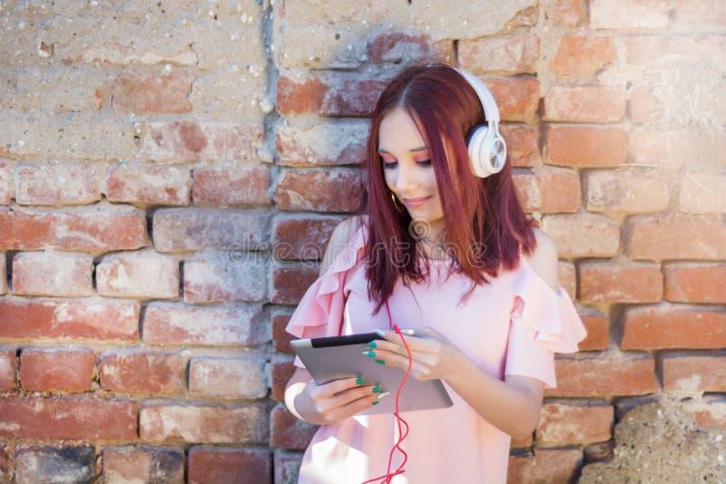 Rödhårig mandam som lyssnar till musik på den digitala minnestavlan med hörlurar mot den utomhus- tegelstenväggen fotografering för bildbyråer