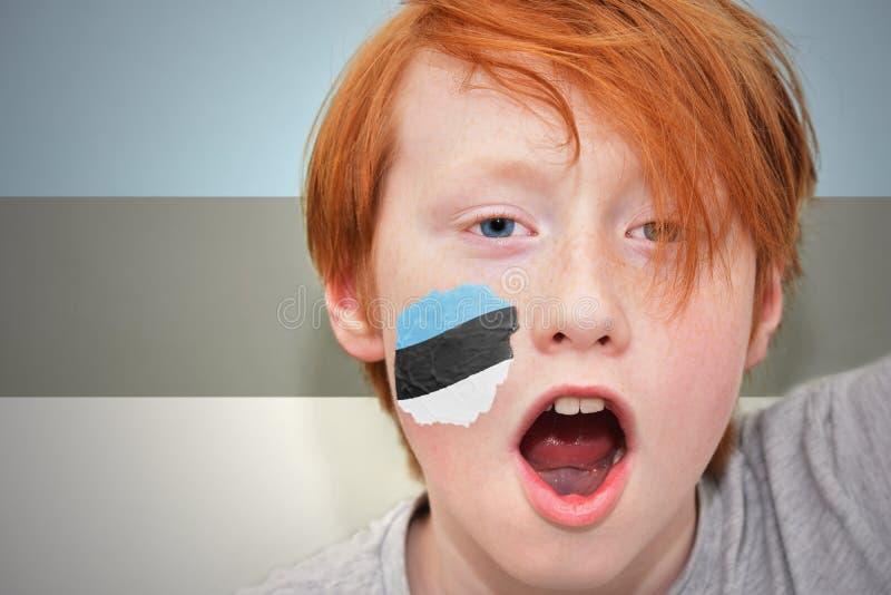 Rödhårig manfanpojken med den estonian flaggan målade på hans framsida royaltyfri fotografi