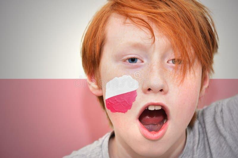 Rödhårig manfanpojken med den polska flaggan målade på hans framsida arkivfoto