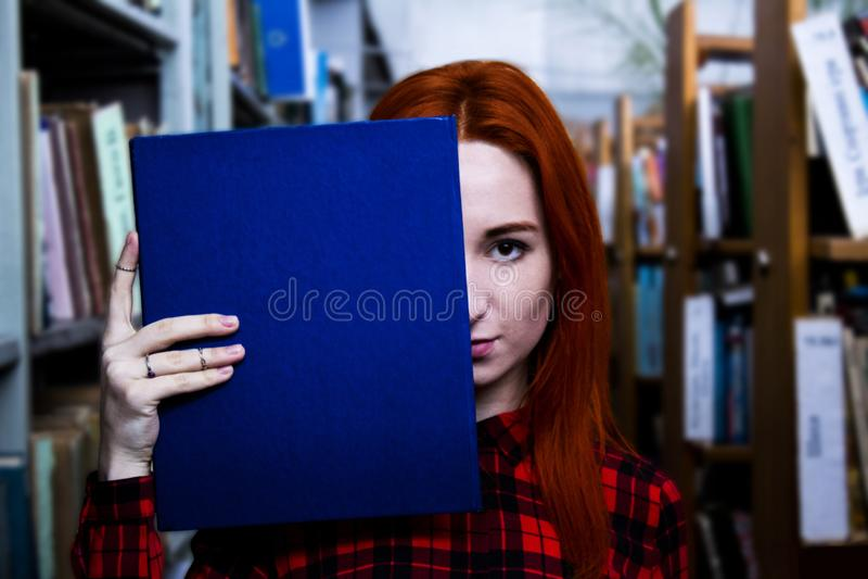 Rödhårig manflicka med den blåa boken i ett arkiv royaltyfri fotografi