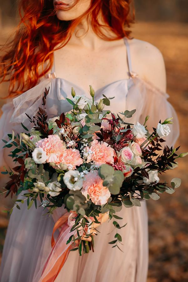 Rödhårig manflicka med fräknar som rymmer en gifta sig bukett arkivfoto