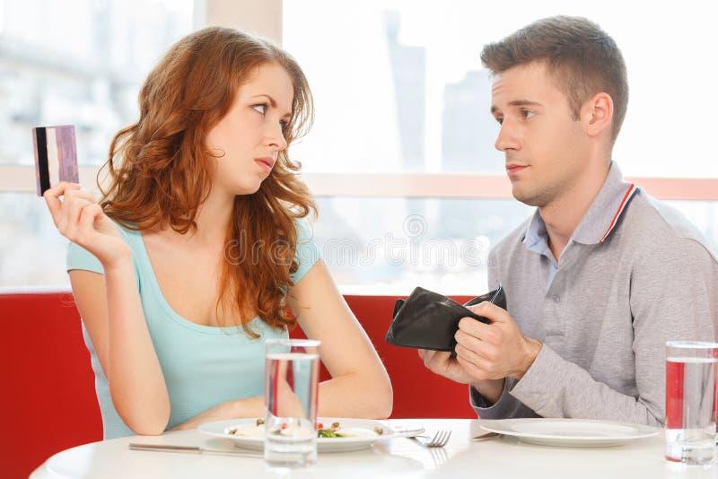 Rödhårig manflicka som betalar för lunch i stället för man arkivbild