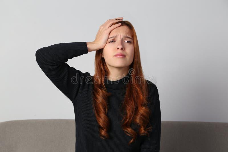 Rödhårig manflickan har en förfärlig headhachemigraine_ på grå bakgrund royaltyfria foton