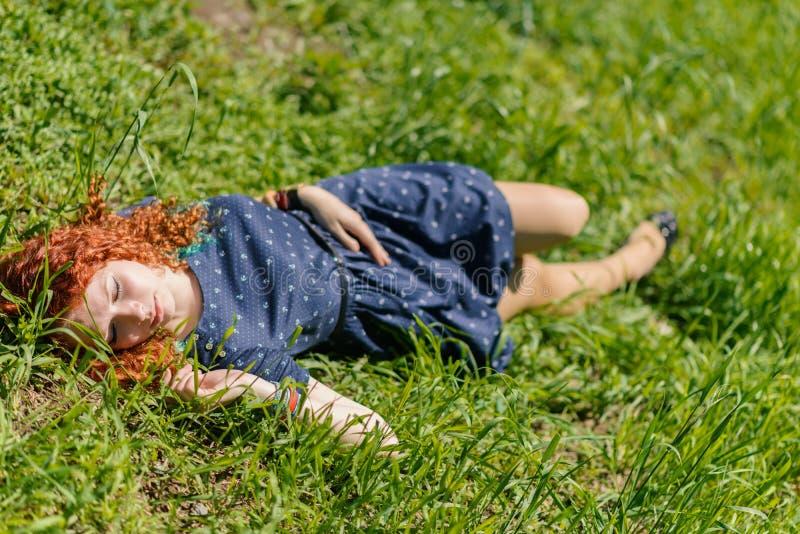 Rödhårig manflickan lägger på gräs royaltyfri fotografi