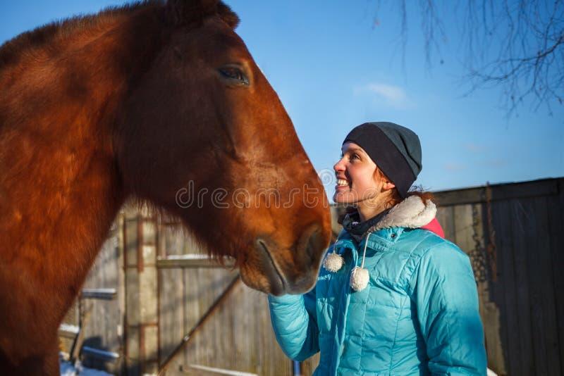 Rödhårig manflickan ler på den röda hästen på en solig vinterdag royaltyfri bild