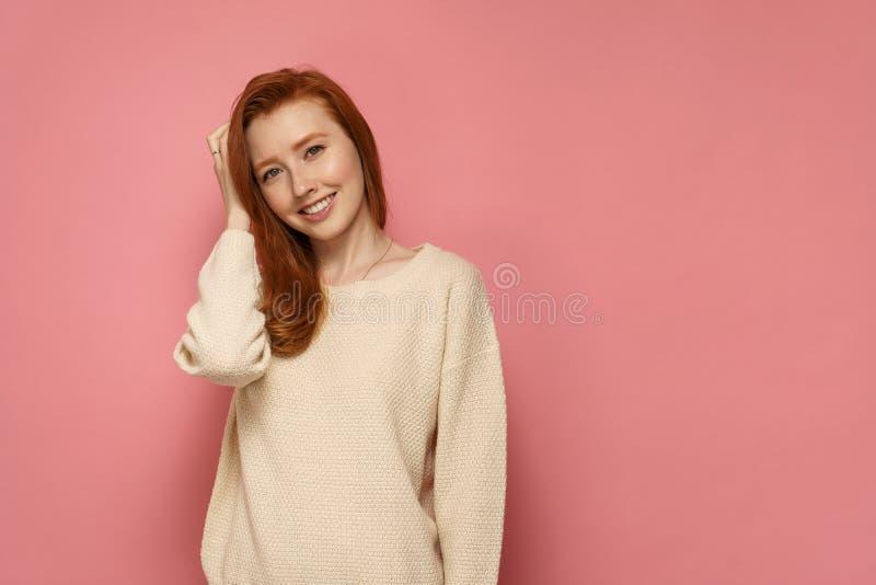 Rödhårig manflickan trycker på hennes hår och leenden på rosa bakgrund royaltyfri fotografi
