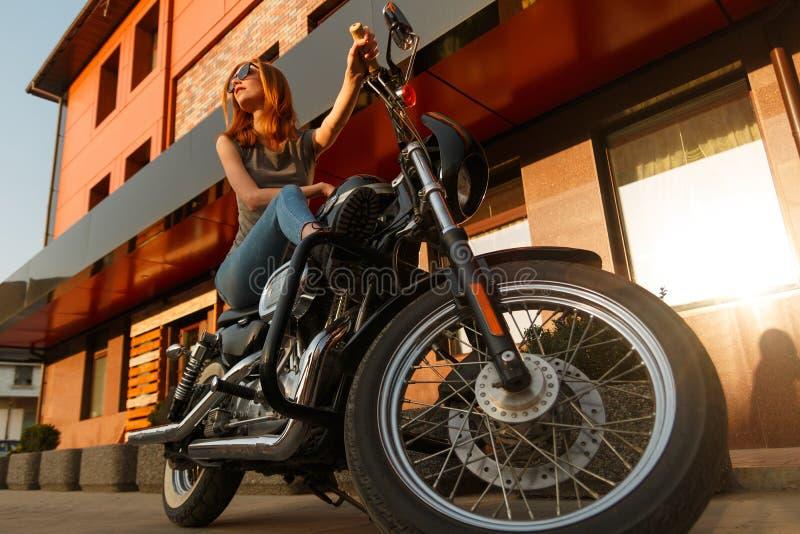 Rödhårig manflickasammanträde på en motorcykel arkivfoto