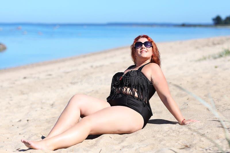 Rödhårig mankvinna i solglasögon som vilar på stranden royaltyfri foto
