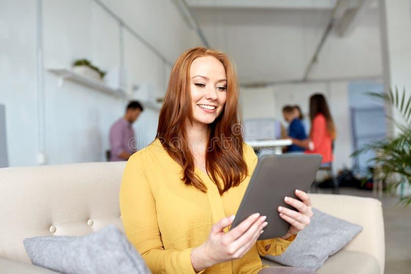 Rödhårig mankvinna med minnestavlaPC:n som arbetar på kontoret fotografering för bildbyråer