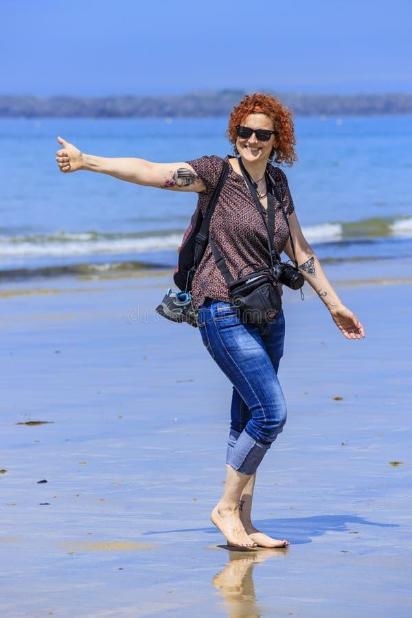 Rödhårig mankvinna på kusten royaltyfri bild
