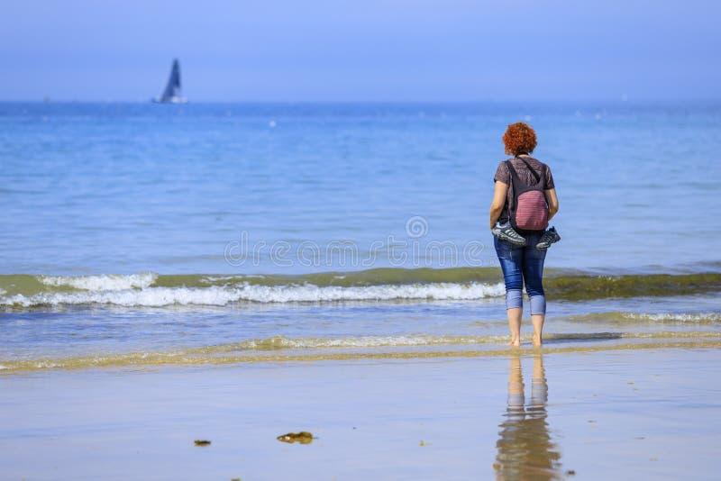 Rödhårig mankvinna på kusten arkivfoton