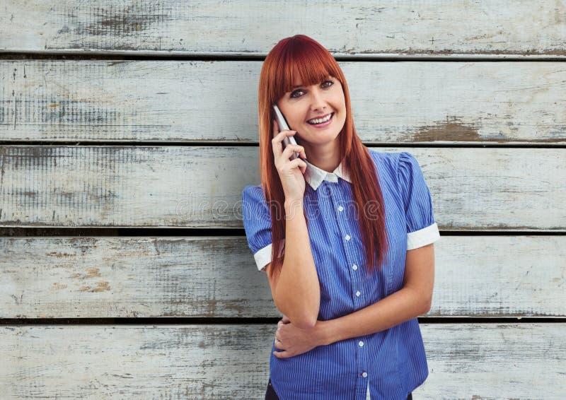 Rödhårig mankvinna som använder mobiltelefonen över träväggen stock illustrationer