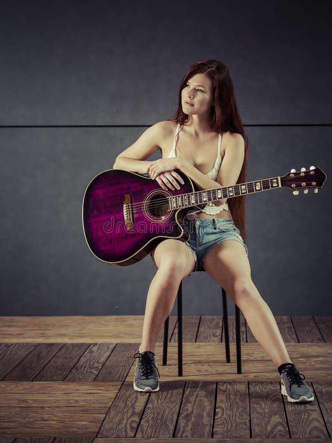 Rödhårig mankvinna som spelar den akustiska gitarren royaltyfri bild