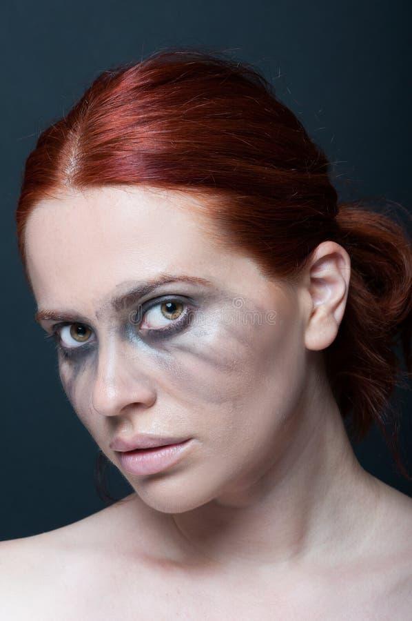 Rödhårig mankvinnlig med smutsig makeup arkivbild