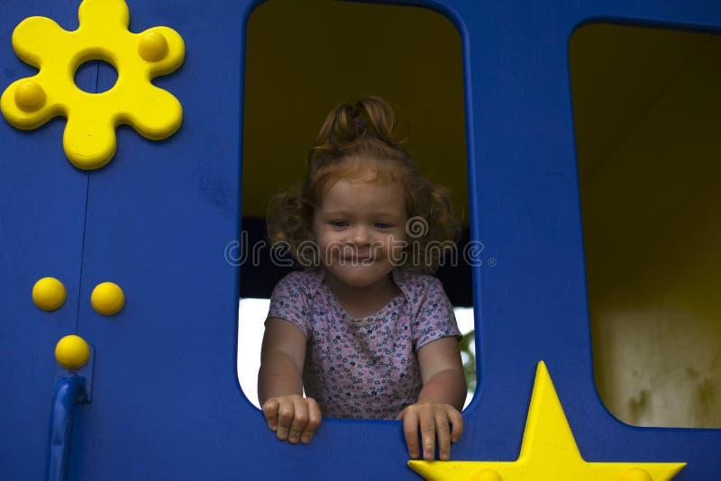 Rödhårig manliten flicka i ett trähus för barn på lekplatsen royaltyfria bilder