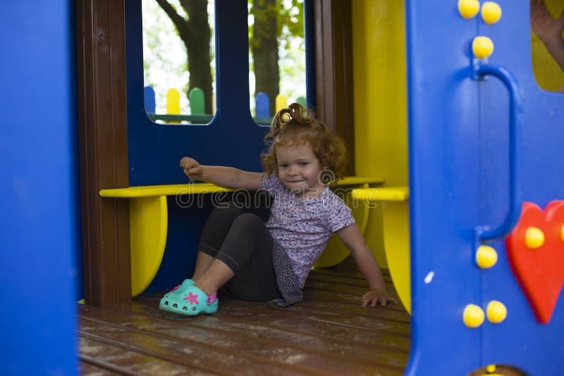 Rödhårig manliten flicka i ett trähus för barn på lekplatsen royaltyfri fotografi