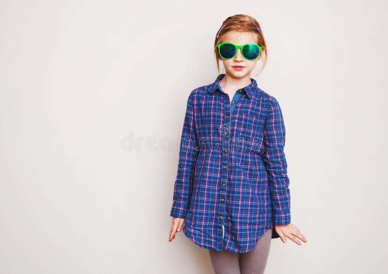 Rödhårig manliten flicka i grön solglasögon som poserar mot väggen arkivfoton