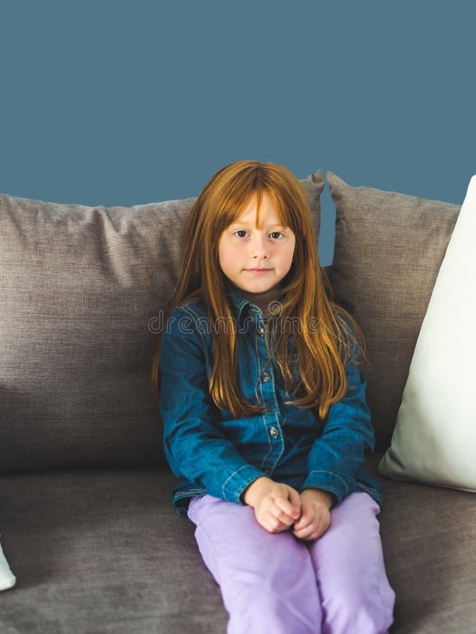 Rödhårig manliten flicka som ser oss som sitter på soffan arkivfoton