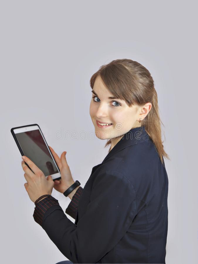 Rödhårig manskolflickan är den hållande digitala minnestavlan med den tomma tomma skärmen isolerat över en grå bakgrund royaltyfria foton